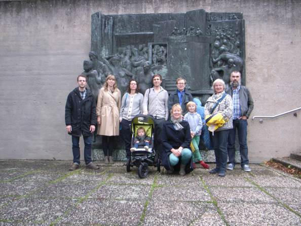 Followers of the tour in front of a bronze wall relief outside the Stadthalle